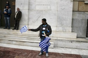 "Street vendor displays Greek national flags for sale in front of the Bank of Greece headquarters during a student parade marking the ""Ohi"" (No) day"