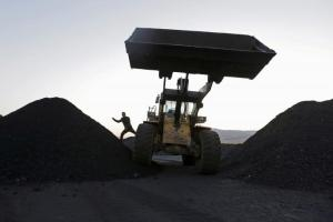 A driver gets off a loading vehicle at local businessman Sun Meng's small coal depot on the outskirts of Jixi in China