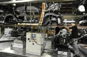 Nissan technicians put an engine into a Qashqai car on the production line at the company's plant in Sunderland