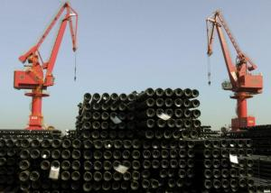 Cranes are seen above piles of steel pipes to be exported at a port in Lianyungang