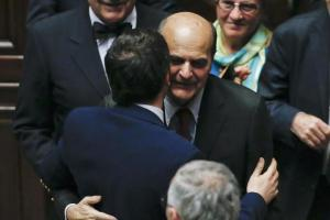 Italy's PM Renzi embraces former PD leader Bersani in the lower house of the parliament during a confidence vote in Rome
